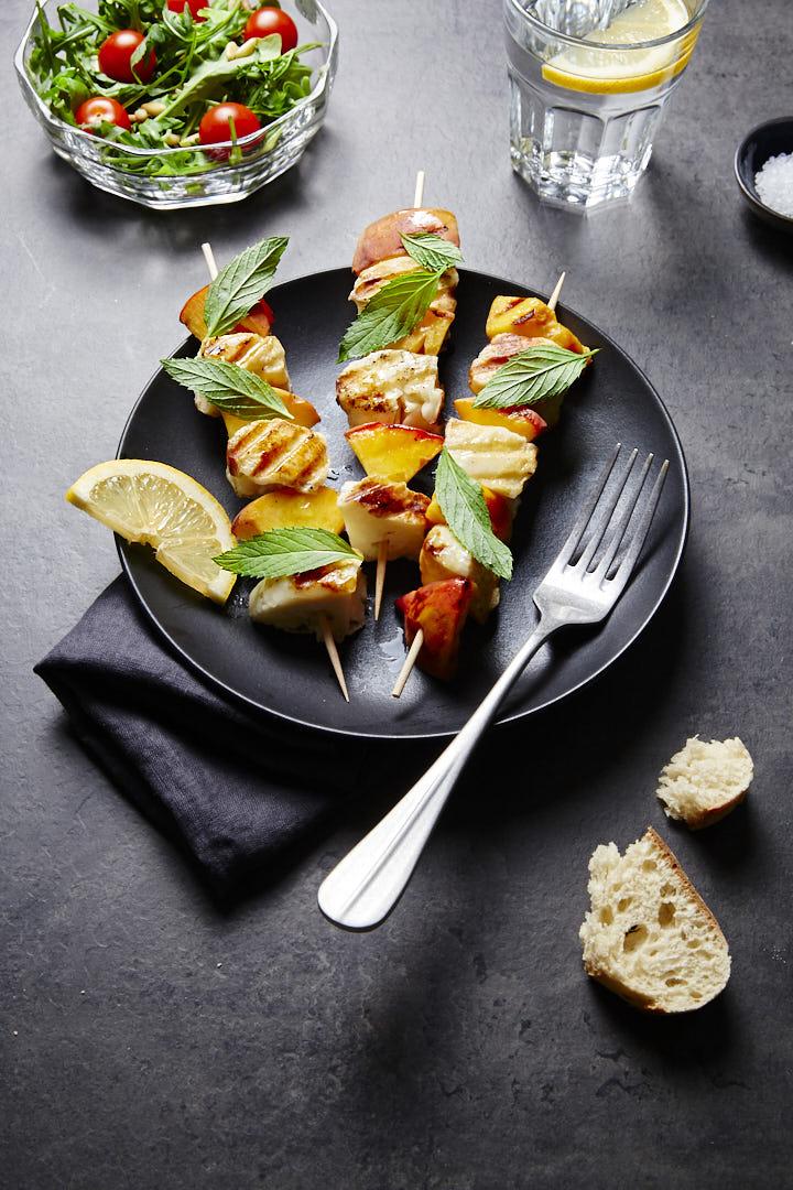 Foodfoto von Halloumi-Pfirsich-Spießen mit Minze dekoriert auf einem schwarzen Teller, eine Gabel liegt auf dem Teller, unter dem Teller liegt eine schwarze Leinenserviette, ein angebrochenes Stück Brot liegt daneben. Am oberen Rand sieht man eine Glasschale mit frischem Salat und ein Glas Wasser mit Zitronenschreibe, der Untergrund ist schwarz marmoriert.