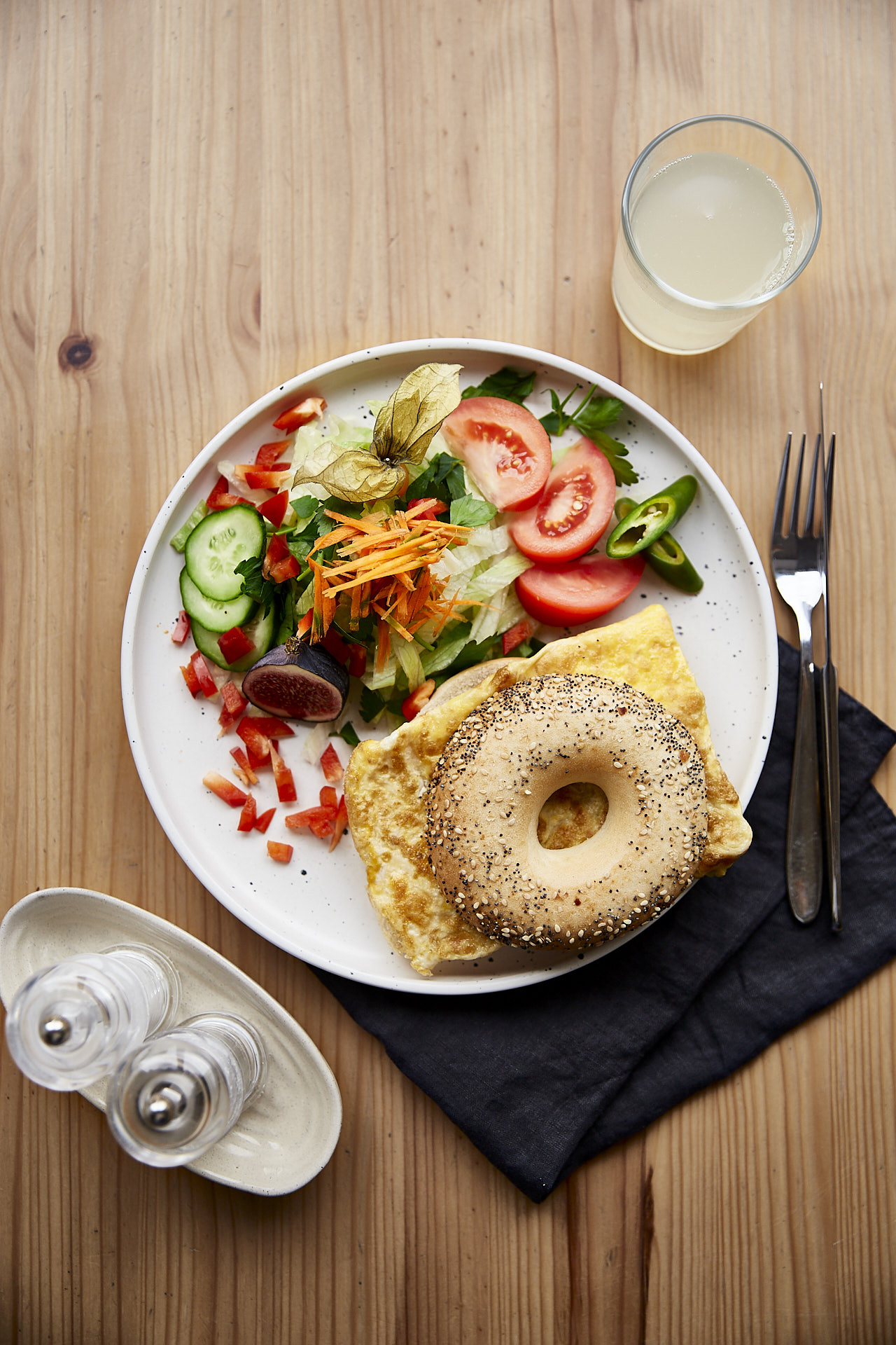 Schönes Food Foto von oben, zeigt einen gedeckten Tisch mit einem Teller mit grünem Salat und einem Bagel, belegt mit Omelette