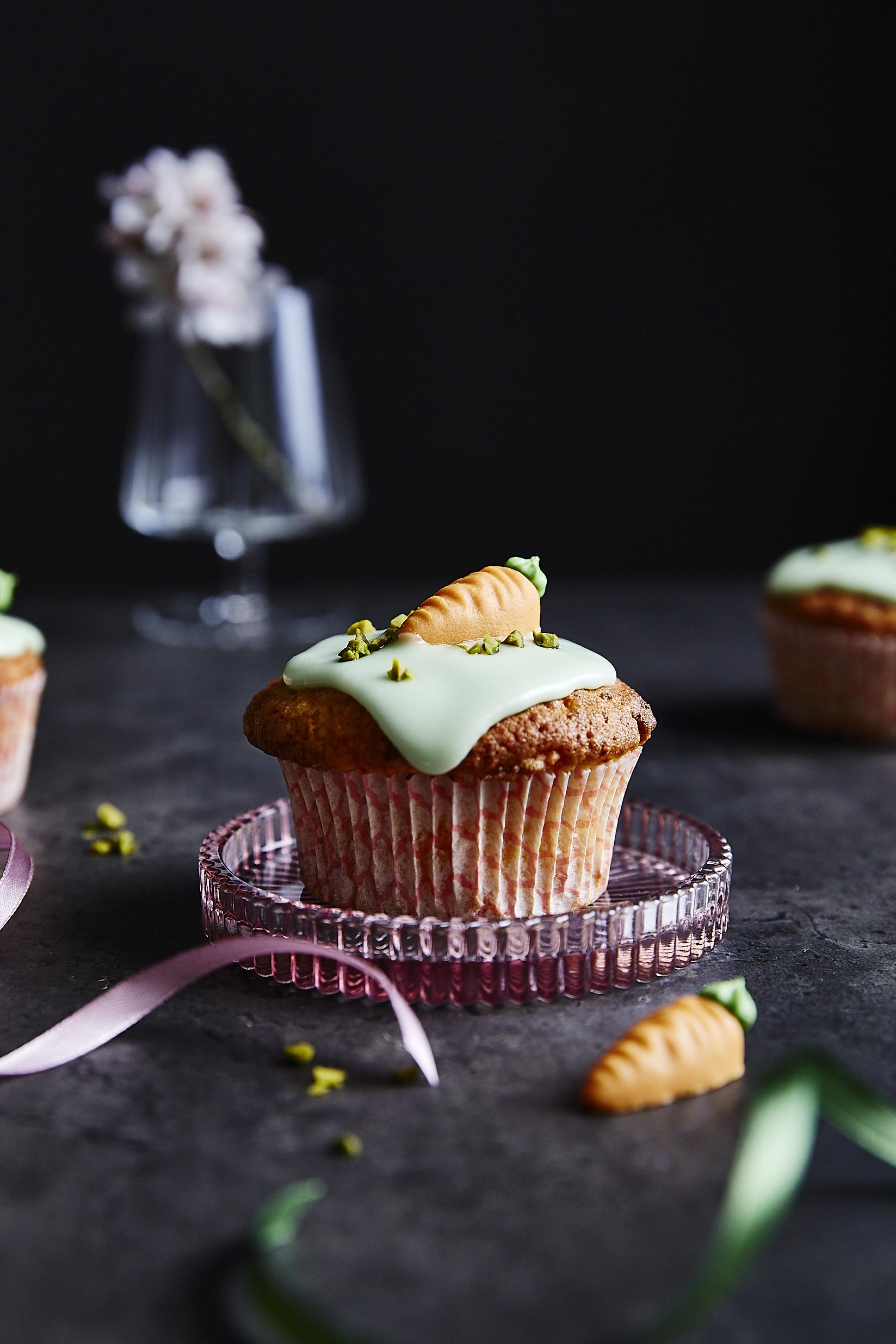 Rübli-Muffin mit grünem Zuckerguss und Karotten-Deko zu Ostern, auf dunklem Untergrund