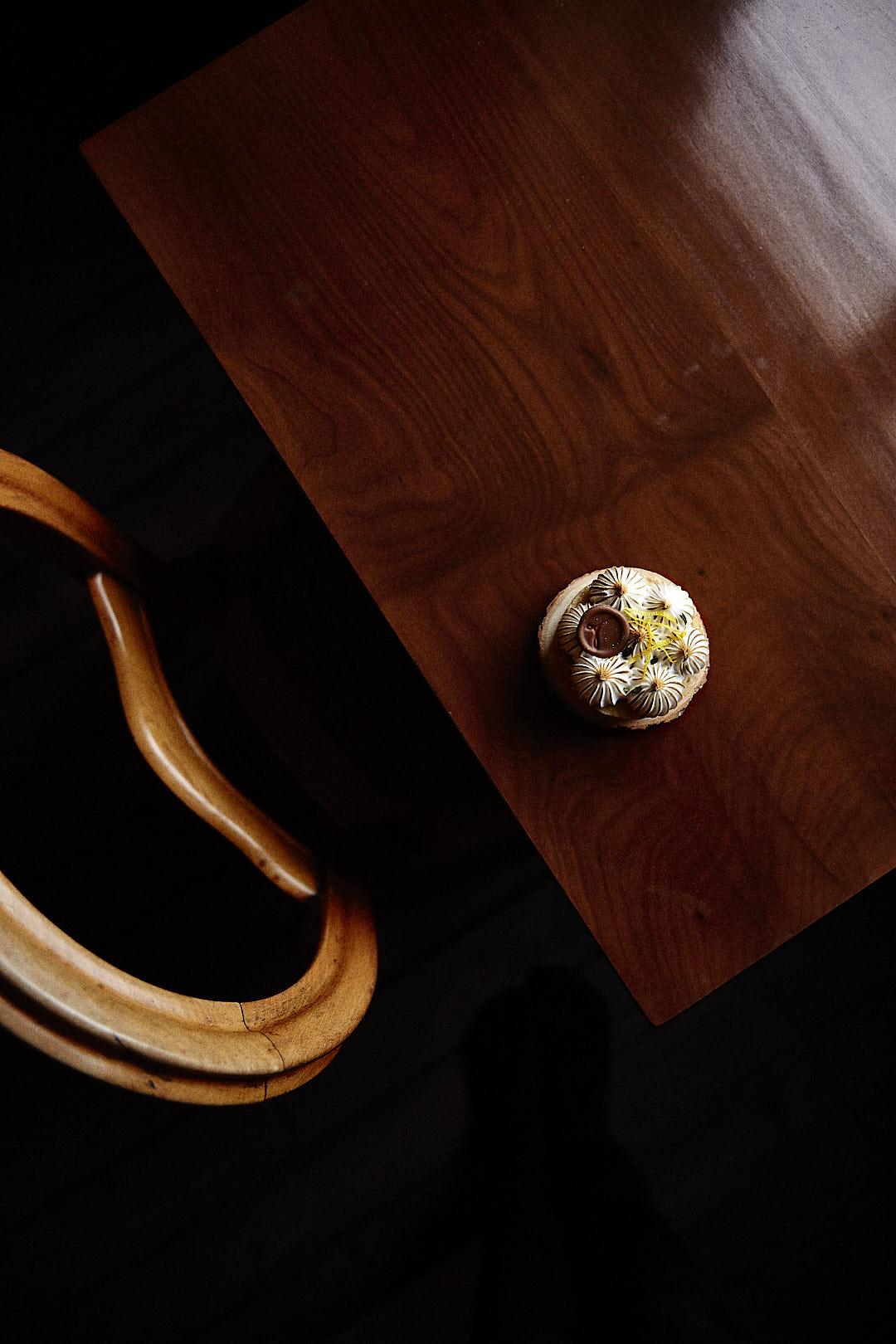 Produktfoto von einem Zitronen-Törtchen von Tartes&Törtchen aus Bielefeld, fotografiert auf einem Holztisch schräg im Anschitt, die Stuhllehne den am Tisch stehenden Holzstuhles ist sichtbar, der Boden liegt im Dunkeln