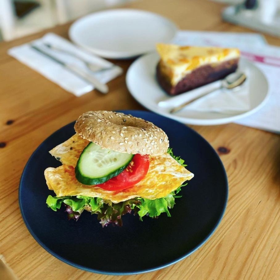 Unprofessionelles Foto gedeckter Tisch, Bagel mit Omelette, im Hintergrund ein Stück Kuchen