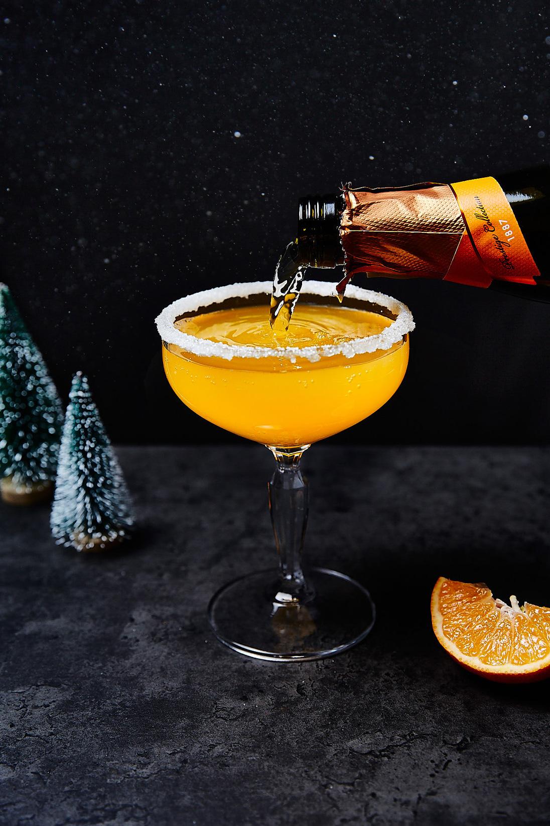 """Food Foto von orange-farbenem Getränk """"Clementine Sprizz"""", Glas wir mit Sekt eingeschenkt, dunkler Untergrund und Hintergrund. Kleine Bäume als Deko-Element."""