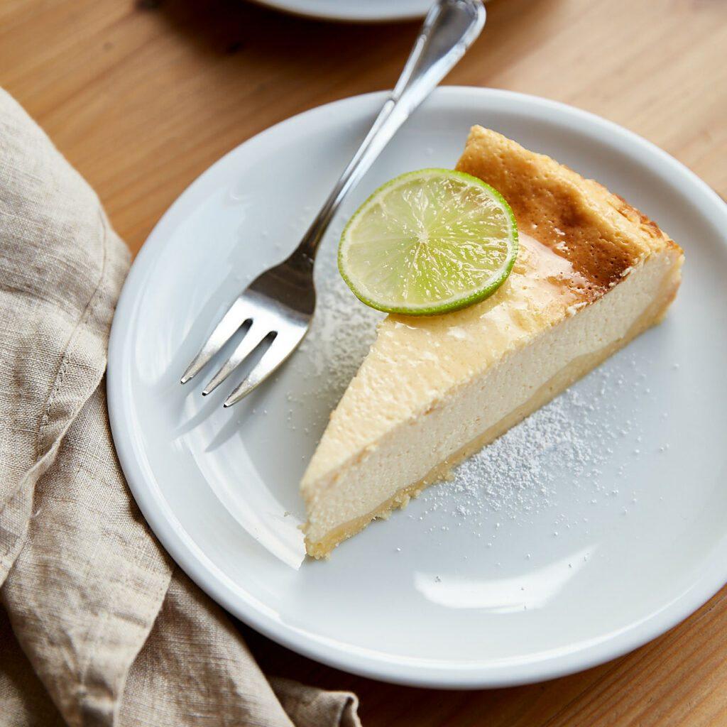 Schönes Food Foto von Käsekuchen mit Limette auf einem weißen Teller angerichtet.