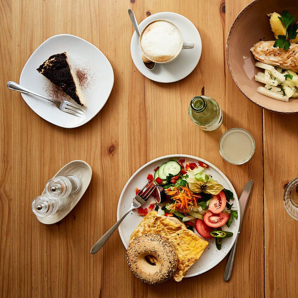 Schönes Foodfoto von gedecktem Tisch aus dem Café Gemach in Bielefeld. Kuchen, Salat, Bagel mit Omelette, Cappuccino und Hähnchen-Gericht aus der Mittagskarte