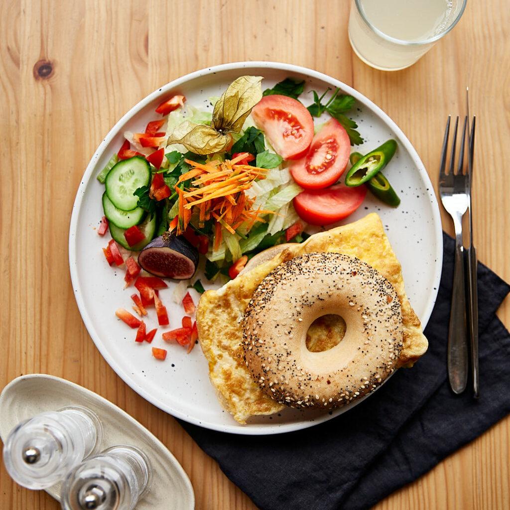 Schönes Food Foto von oben, der Fotografin Nadja Kuschel, zeigt einen gedeckten Tisch mit einem Teller mit grünem Salat und einem Bagel, belegt mit Omelette