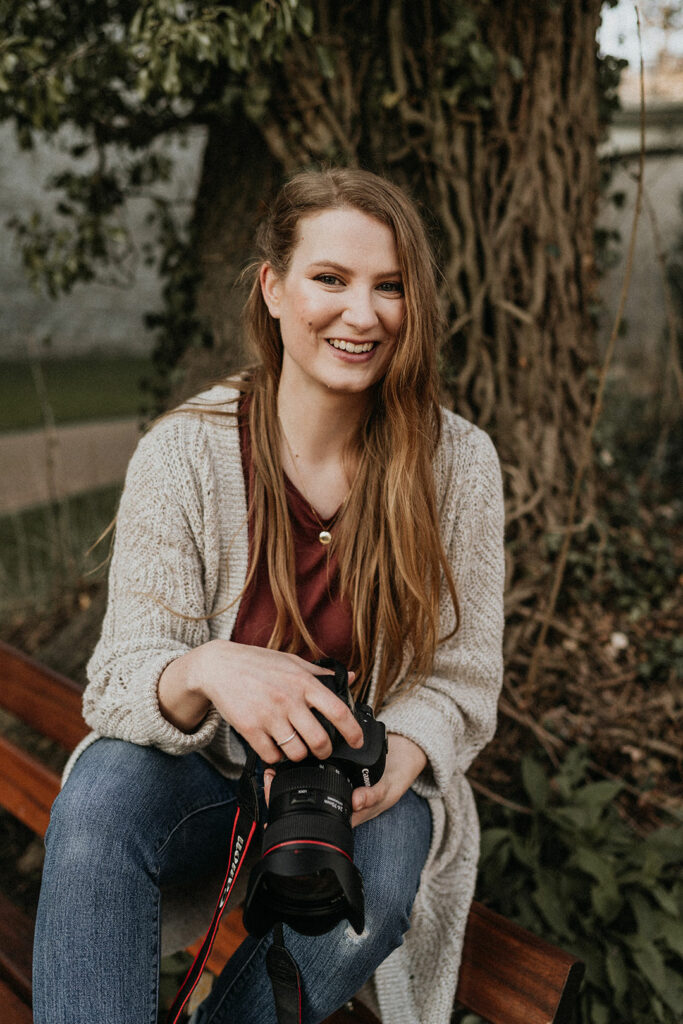 Portrait von Nadja Kuschel, Foodfotografin, bei dem sie den Betrachter in die Augen schaut. Sie hält ihre Kamera in der Hand, aufgenommen vor einem Baum auf einer Bank