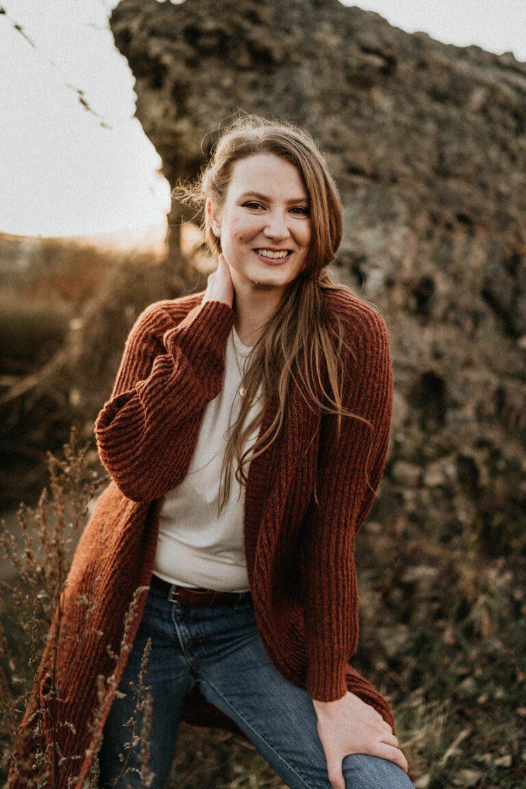 Selbstbewusstes Halb-Total-Portrait von Nadja Kuschel, eine Hand ist auf ihr Bein gestützt, die andere Hand liegt in ihrem Nacken, Blick in die Kamera mit einem Lächeln, Abendsonne, Licht kommt von hinten links